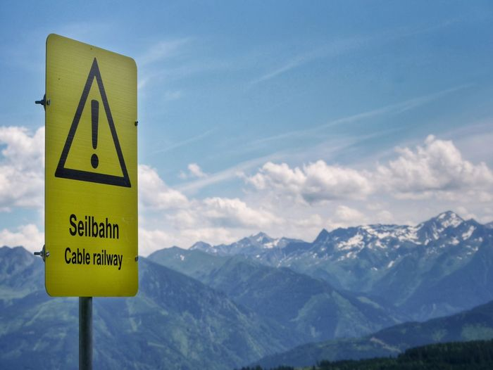 Information sign against mountains and sky
