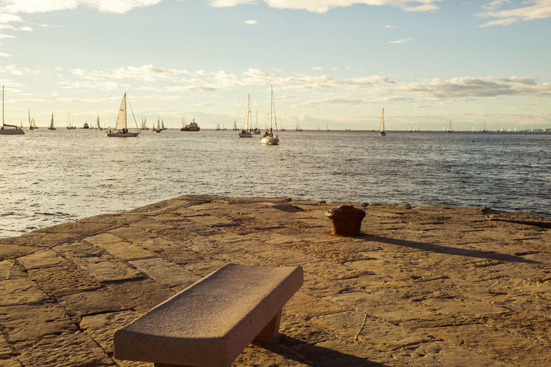 Seat On Pier With Sailboats On Sea In Background
