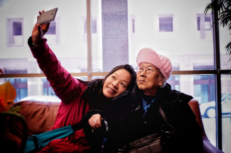 Smiling mid adult woman taking selfie with mother