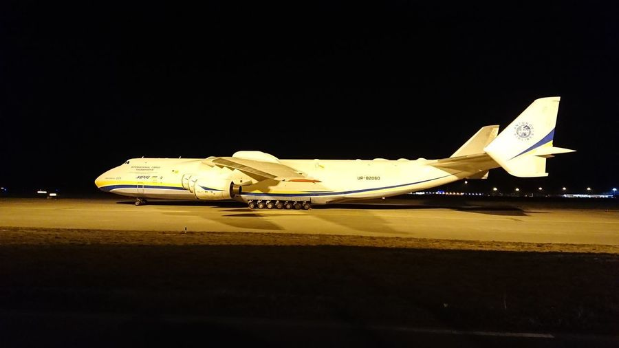 Side view of airplane at airport runway against sky at night