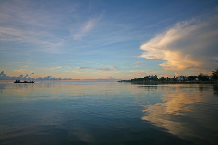 A ship passes in the distance off Negros Island, the Philippines The Philippines Beauty In Nature Cloud - Sky Day Dumaguete City Nature Nautical Vessel No People Outdoors Reflection Scenics Sea Sky Sunrise Tranquil Scene Tranquility Water Waterfront