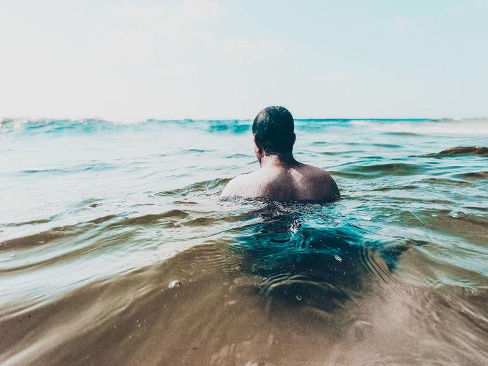 Rear view of shirtless man swimming in sea