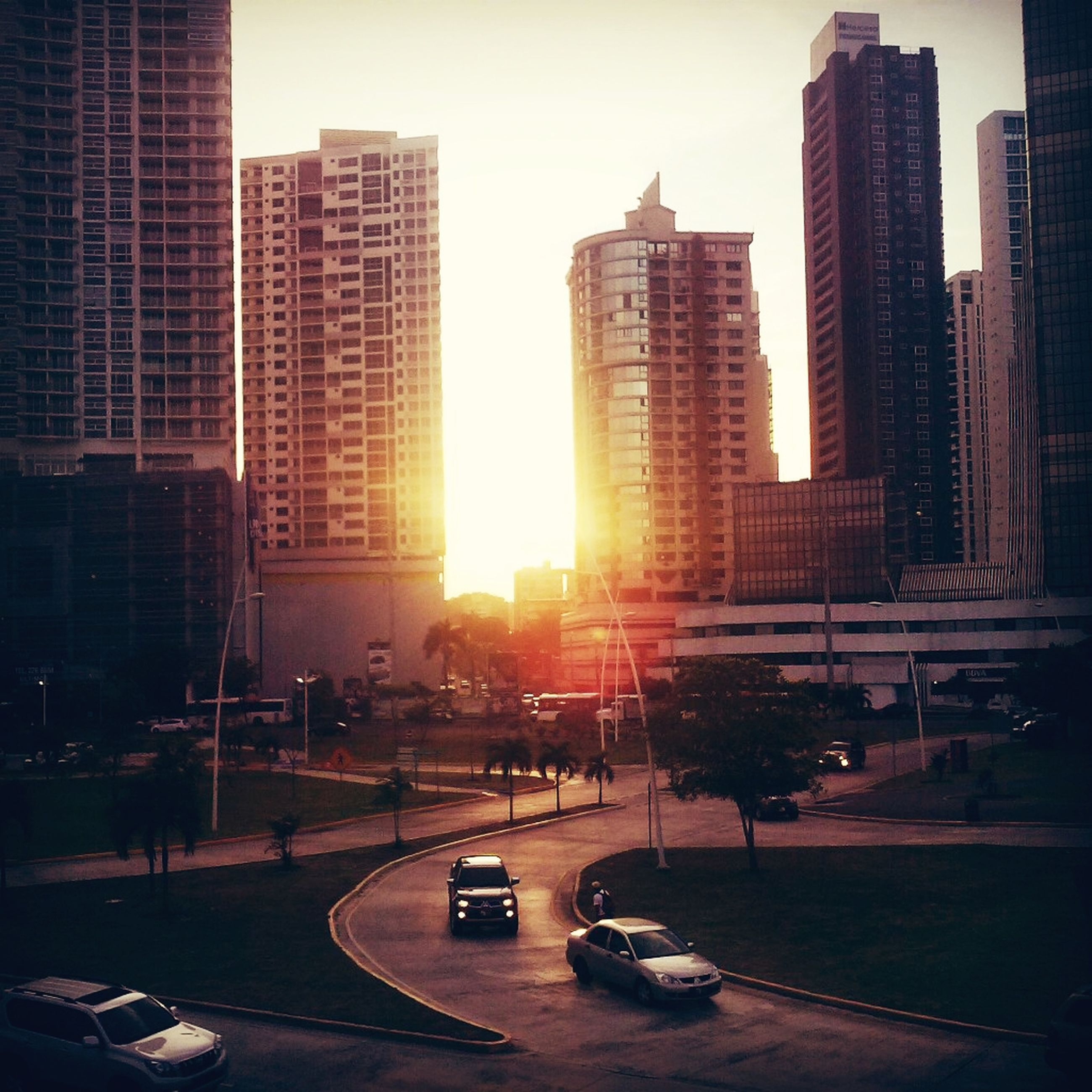 building exterior, architecture, city, built structure, skyscraper, sunset, transportation, office building, car, street, sun, modern, road, tall - high, sunlight, tower, building, city life, land vehicle, city street