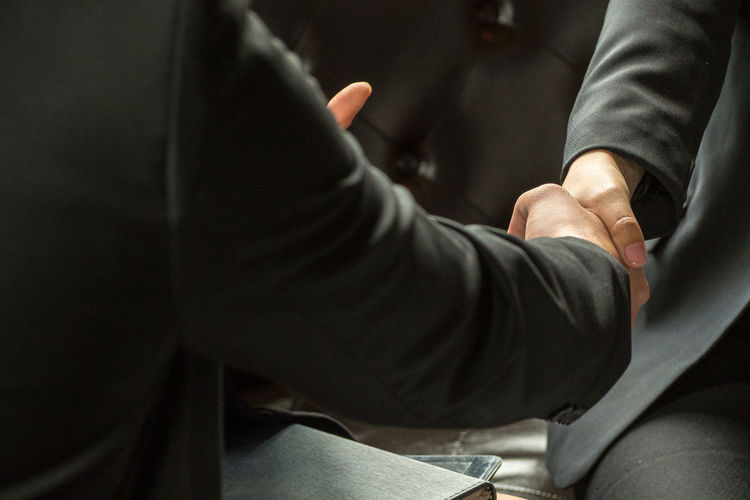 Midsection Of Businessman Shaking Hands With Male Coworker In Office