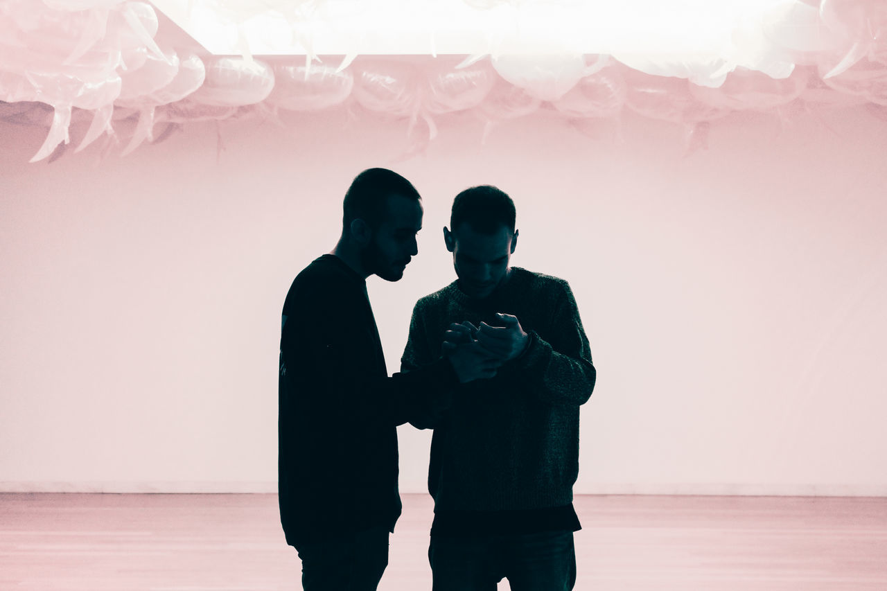 MEN IN COUPLE STANDING AGAINST WALL