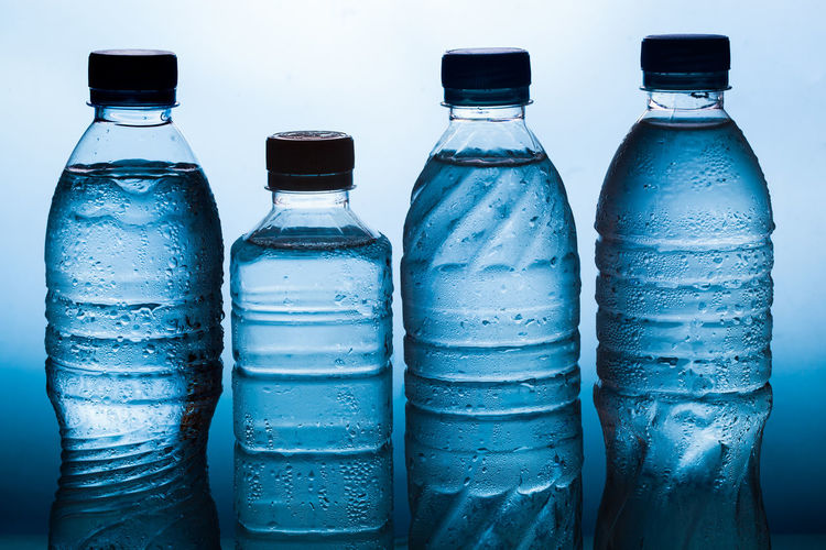 Close-up of bottles on table against blue background