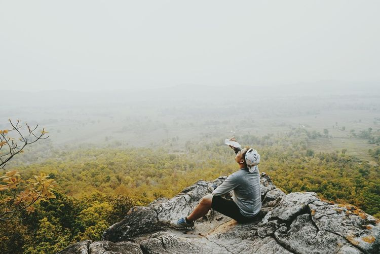 High angle view of male hiker pouring water on face while sitting on cliff