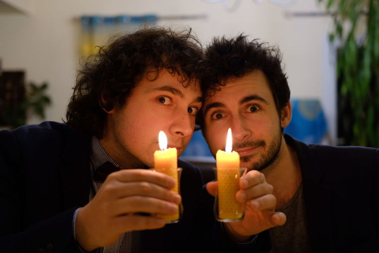 Portrait of friends with illuminated candles at home