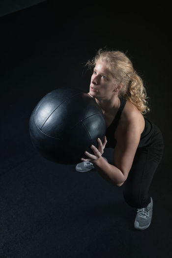 Young Woman Exercising With Medicine Ball Against Black Background