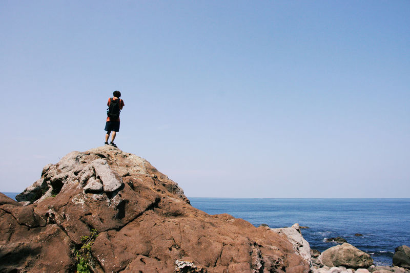 Rear view of man standing on cliff