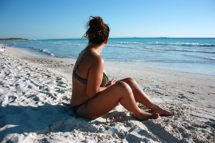 Caucasian girl in a bathing suit sunbathes by the sea in the summer in a tuscany beach