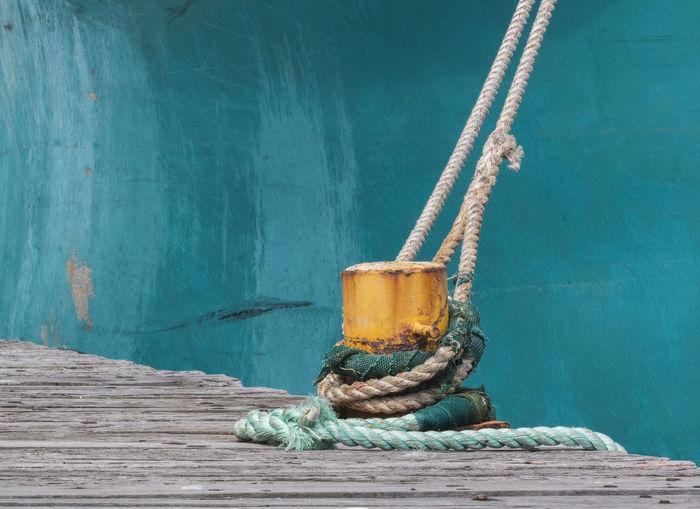 Close-up of rope tied on bollard on peer
