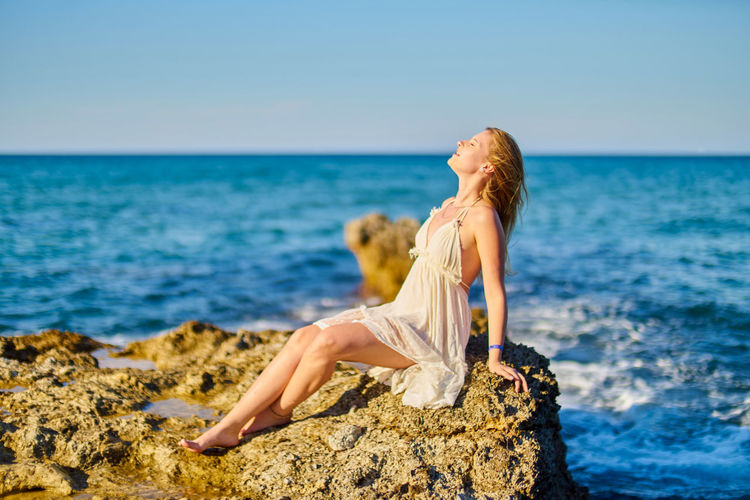 Woman Relaxing On Rock At Beach