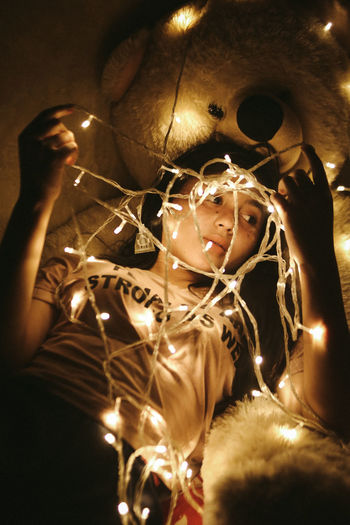 Low angle view of woman with illuminated christmas lights