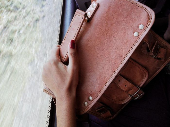 Close-up of hand holding leather bag