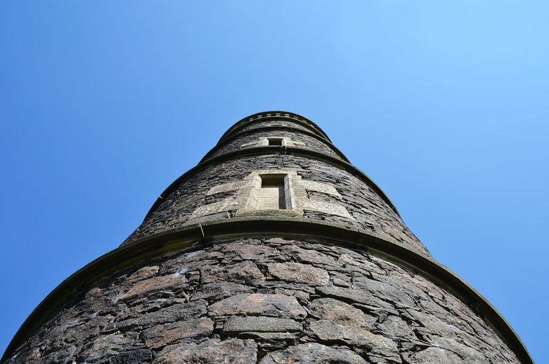 Low angle view of old tower against clear blue sky