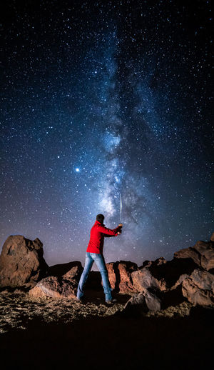 Full length of man standing on rock at night