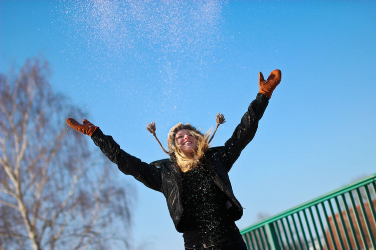 Happy Young Woman Throwing Snow Against Clear Blue Sky