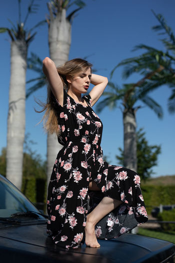 Full length of woman crouching on vehicle hood against sky