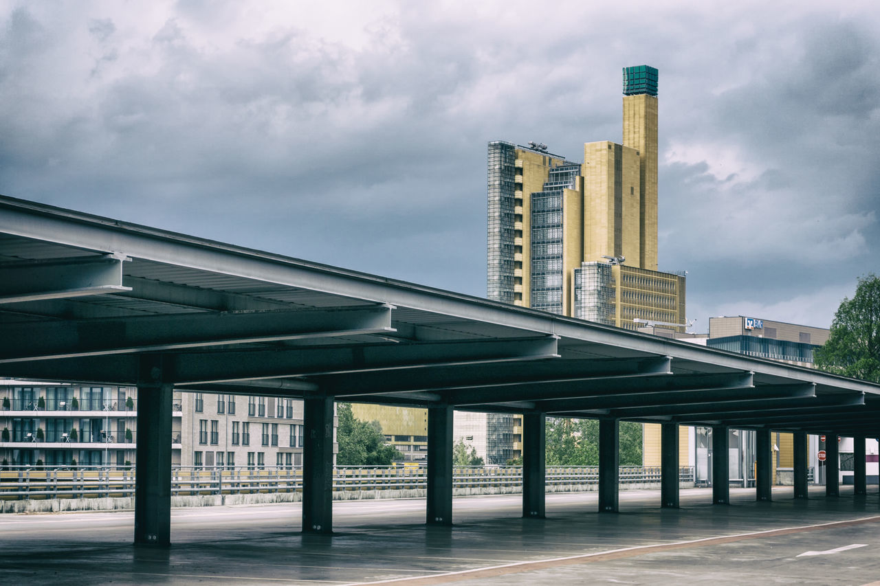 architecture, built structure, building exterior, sky, cloud - sky, skyscraper, day, city, no people, outdoors, bridge - man made structure, architectural column, travel destinations, transportation, modern, low angle view