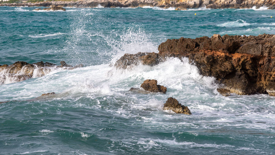 Waves splashing on rocks in sea