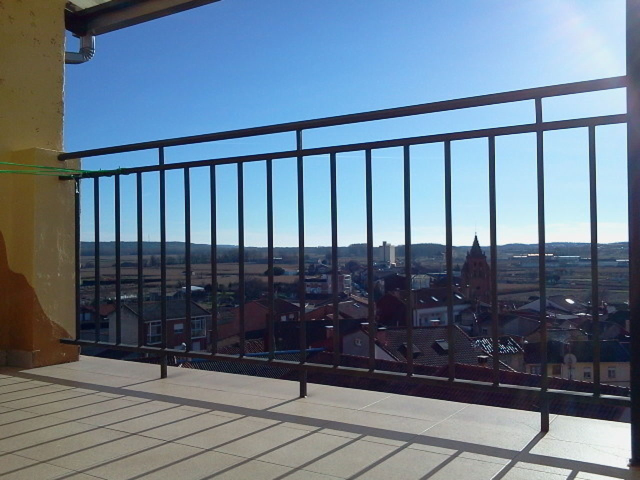 railing, day, clear sky, outdoors, sky, sunlight, architecture, built structure, no people, city