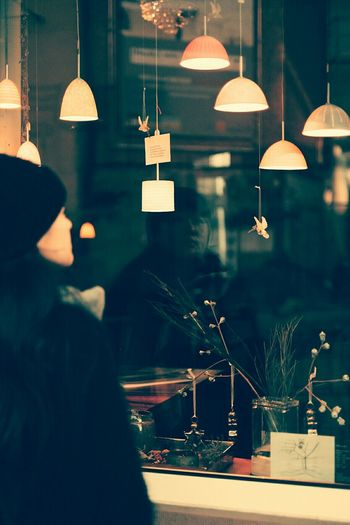 Woman looking at illuminated pendant lights on window display
