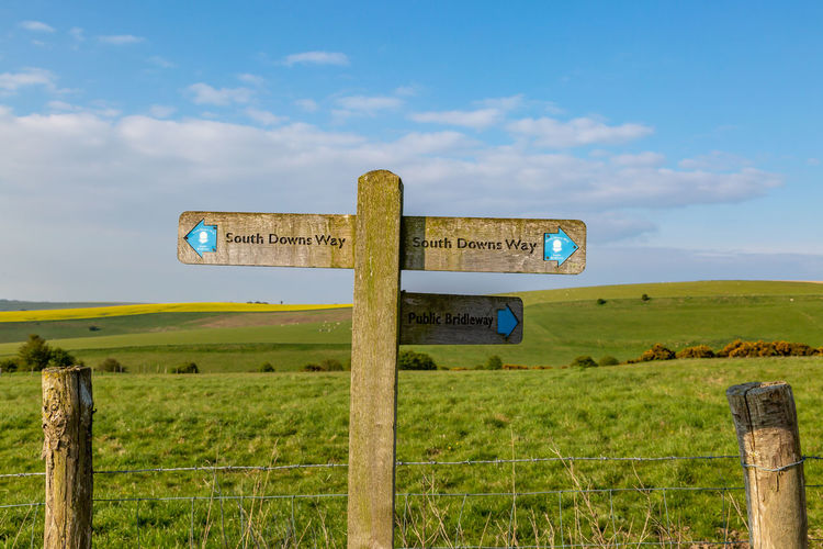 A South Downs Way directional sign in Sussex, on a sunny spring morning Sussex Sign Post South Downs South Downs Way Sign Sky Grass Land Field Communication Nature Plant Landscape No People Day Guidance Cloud - Sky Green Color Information Environment Information Sign Arrow Symbol Symbol Directional Sign Outdoors Post Wooden Post