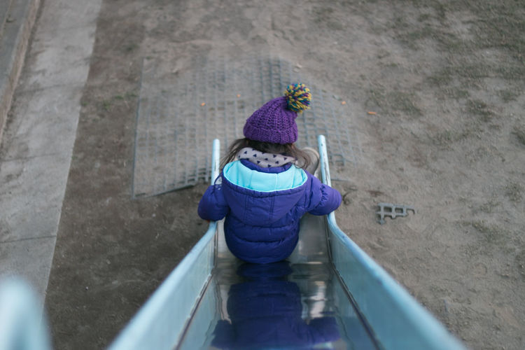 High angle view of girl on slide in playground