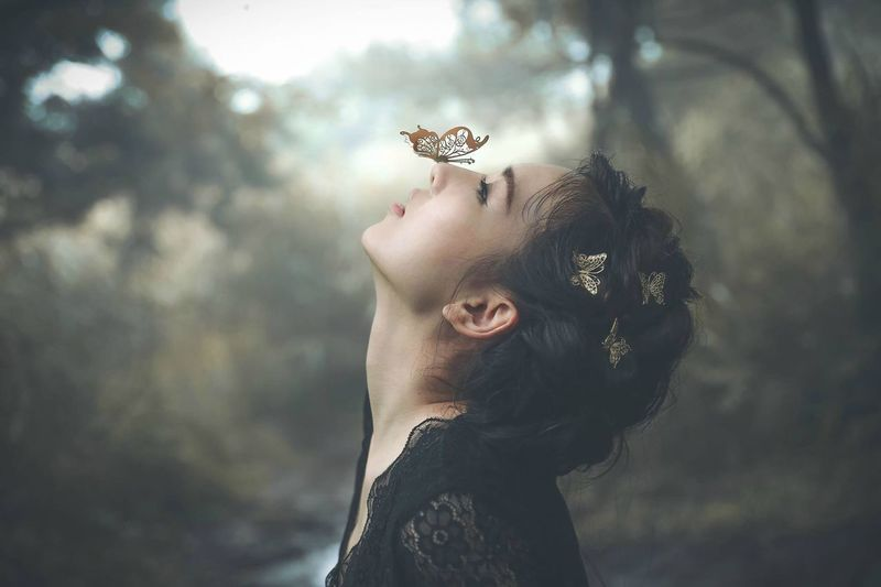 Side view of young woman with butterfly on nose in forest