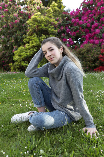 16 year old teenager sitting in a park with grass and flowers, taken in Limoges, France. 16 Years Spanish Woman Adolescent Casual Clothing Day Full Length Grass Innocence Leisure Activity Lifestyles Looking At Camera Nature One Person Outdoors person Plant Portrait Real People Relaxation Sitting Teen Teenager Teenagers Only Young Women