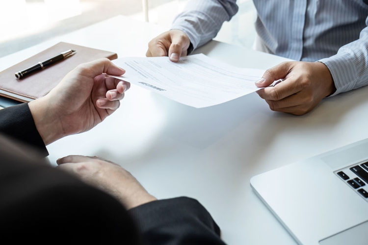 High angle view of candidate giving resume to manager while sitting on table in office