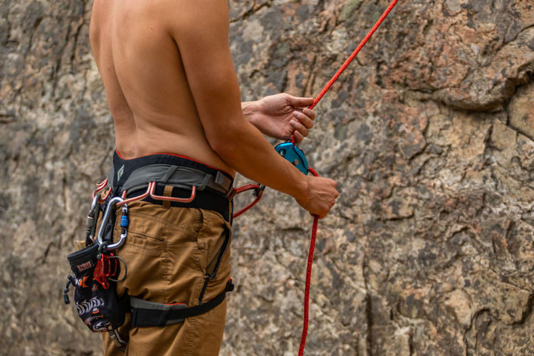 Rear view of man with rope on rock