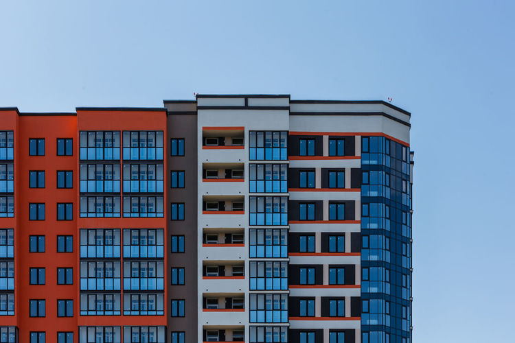 New high rise apartment building with many balcony and windows on blue sky with clouds background