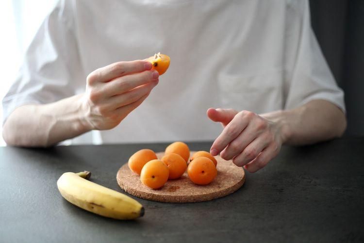 Cropped image of man holding orange fruit