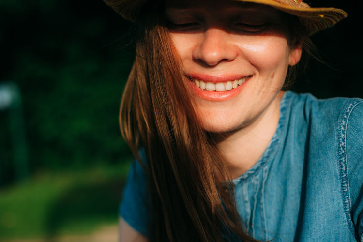 Close-up of smiling young woman wearing straw hat