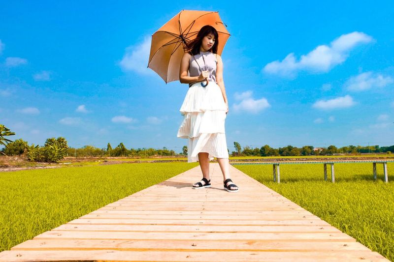 Full length of woman holding umbrella while standing on boardwalk over field against sky