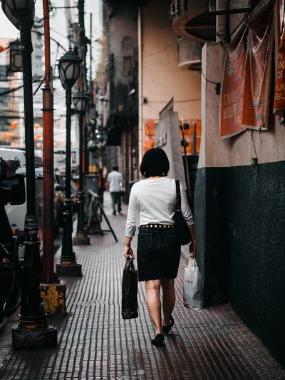 Uwian na. Full Length Real People Rear View One Person Architecture Lifestyles Walking Women Building Exterior Adult Casual Clothing Day Outdoors Footpath City The Street Photographer - 2018 EyeEm Awards