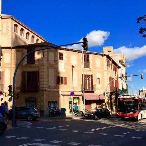 Cars on street in city against blue sky