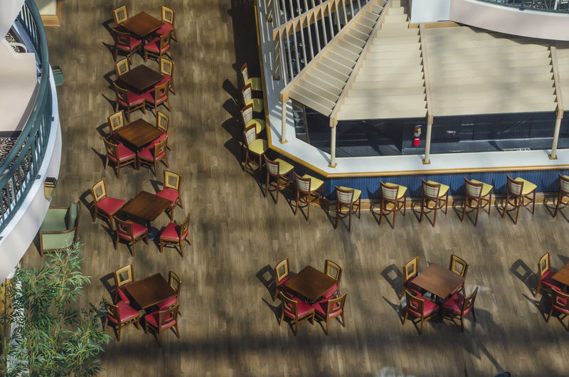 High Angle View Of Empty Chairs And Tables In Restaurant During Sunny Day