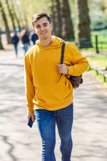 Young urban man using smartphone walking in street in an urban park in London, UK. Looking At Camera Portrait Smiling One Person Casual Clothing Yellow Lifestyles Front View Happiness Leisure Activity Real People Focus On Foreground Day Three Quarter Length Standing Emotion Jeans Men Nature Outdoors