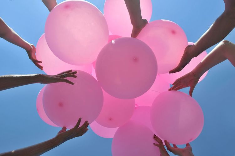 Low angle view of pink balloons against sky