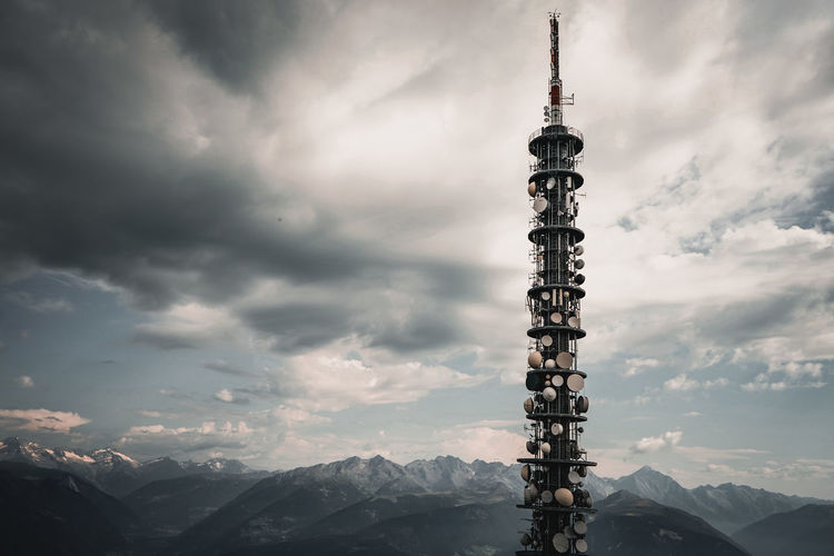 Communications tower against cloudy sky