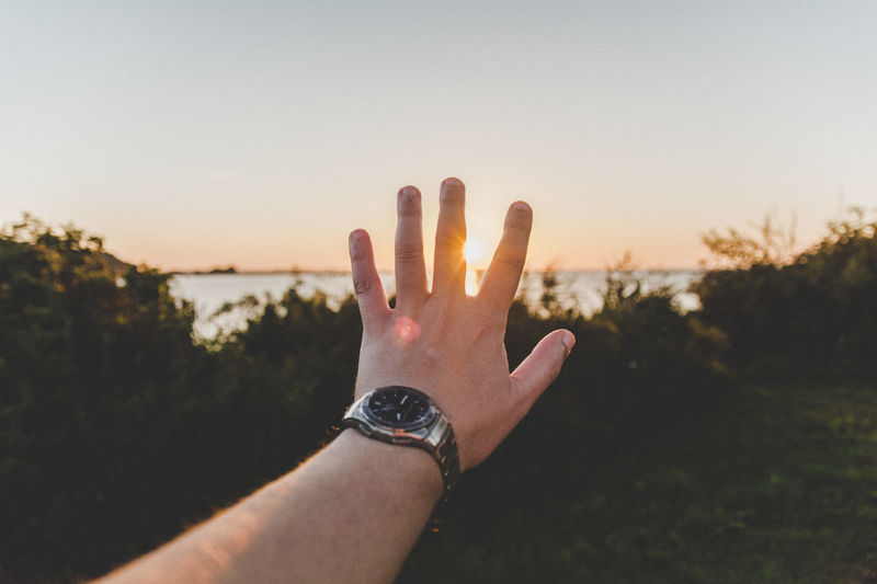 Arm Hand Horizon Human Finger Human Skin Nature Outdoors Person Personal Perspective Reaching Sky Sun Sundown Sunset Water