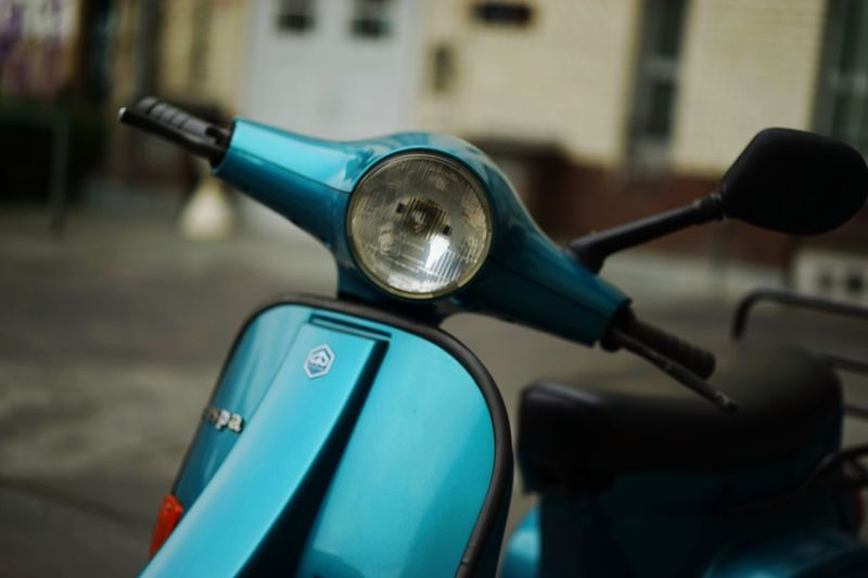Close-up of cropped scooter on blurred road
