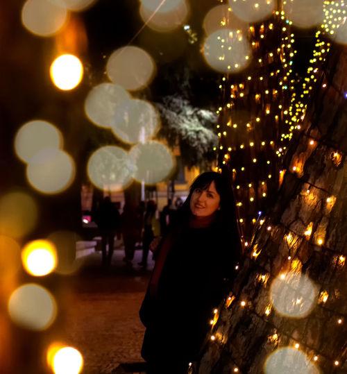 Woman standing by illuminated christmas tree at night