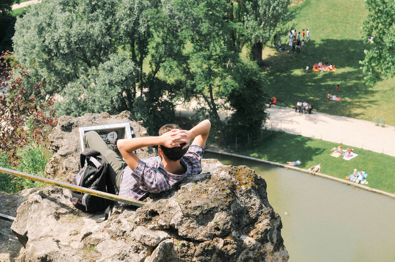 High angle view of man reclining on rock formation at park