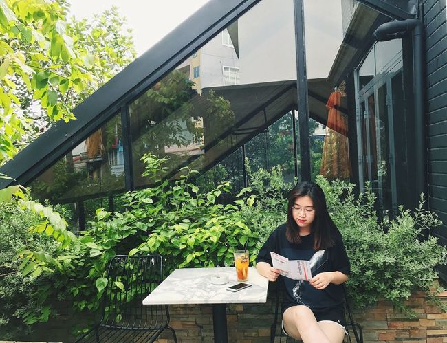 Hanoi Vietnam Thecoffeehouse One Person Sitting Only Women FreeTime Day Lifestyles Outdoors Green Green Color Tree House Readbooks