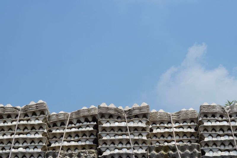 Low Angle View Of Egg In Stacked Cartons Against Sky