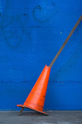 Broken traffic cone on sidewalk against blue wall